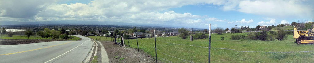 a paved road runs along side a green field overlooking the city of San Jose and the Southern Bay Area