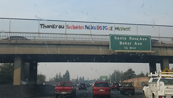 Banner in Santa Rosa thanking the firefighters, police, EMS, PG&E, and military personnel, hanging over a freeway overpass.