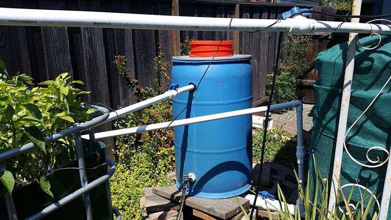 Blue barrel with orange insert, and several white pipes extending out the side.